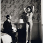 Un homme assis sur le lit d'une chambre d'hôtel regarde une femme nue se présentant devant lui, ne portant que des chaussures à talons (une photo d'Helmut Newton)