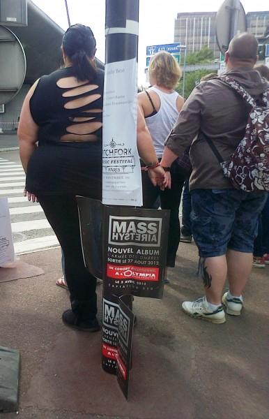 Un couple obèse à côté d'une affiche pour un concert de Mass Hysteria