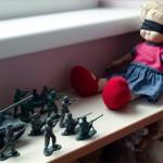 Des soldats de plomb mettent en joue une poupée, les yeux bandés, dans un peloton d'exécution