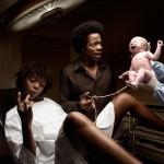 Scène d'accouchement. Une femme noire accouche d'un bébé blanc auprès de son mari noir. Elle se regarde les ongles en sifflotant tandis qu'une expression de stupeur se lit sur son compagnon