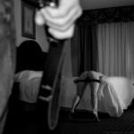 Un homme, une ceinture à la main, devant une femme nue sur un lit, tendant ses fesses