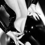 Une femme de dos dézippe sa combinaison latex jusqu'à ses fesses