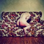 Femme nue, assise de dos sur un canapé fleuri, cul rougi