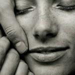 Un visage de femme, les yeux fermés, caressé par les mains d'un homme