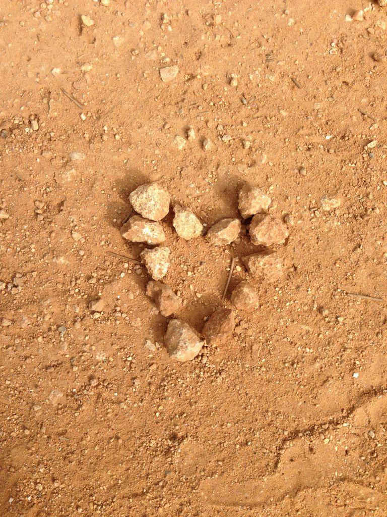 cœur en cailloux sur un sol ocre