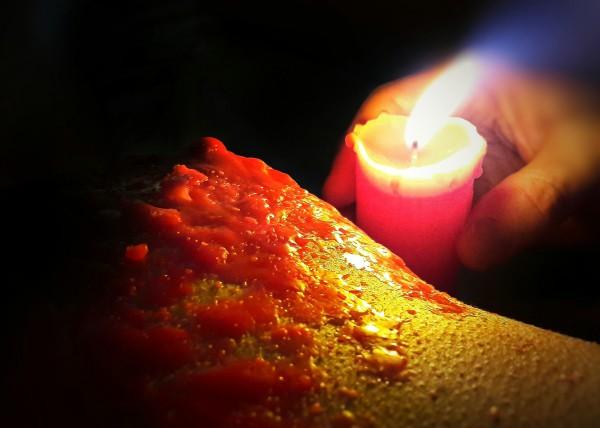Un sein couvert de cire rouge, une bougie, une main