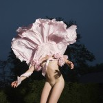 Dans la nuit, une femme dont la robe se relève, la dévoilant nue et masquant son visage