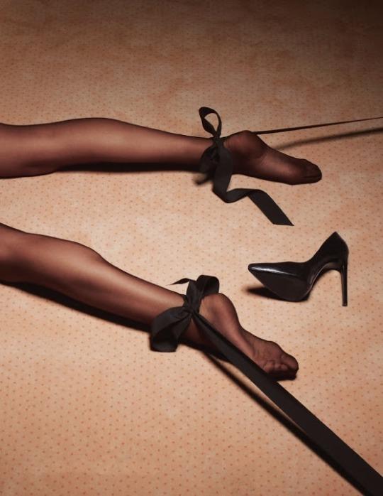 On ne voit de cette femme alongée sur le ventre, sur la moquette d'une chambre d'hôtel, que ses eux jambes gainées de soie, écartées par deux liens de satin noir. Un escarpin noir complète la scène.