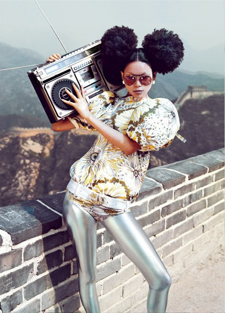 Une jeune femme à la mode tient un soundblaster sur la muraille de Chine